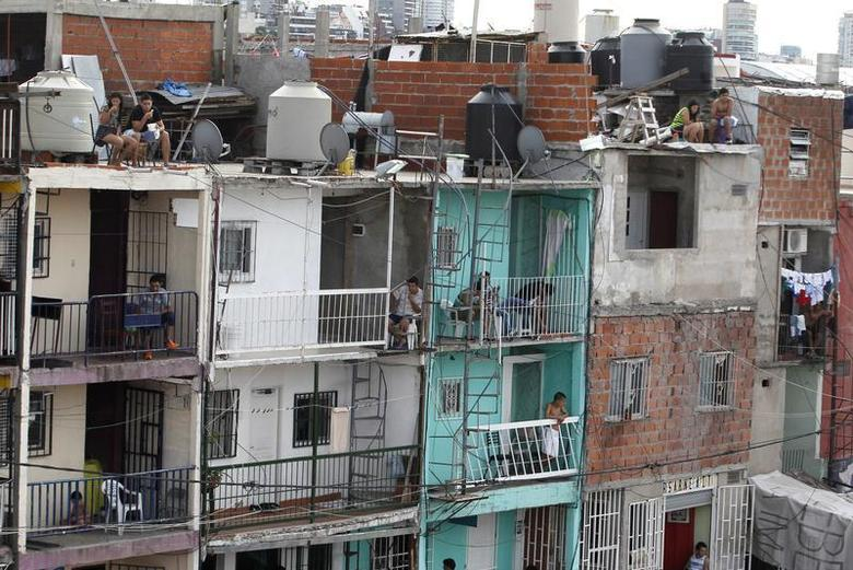 Residents are seen in the Villa 31 slum, which censuses show has grown 50 percent in the past four years to currently house some 40,000 people, near the 100-year-old railway station Retiro in the heart of Buenos Aires, February 9, 2014. REUTERS/Enrique Marcarian