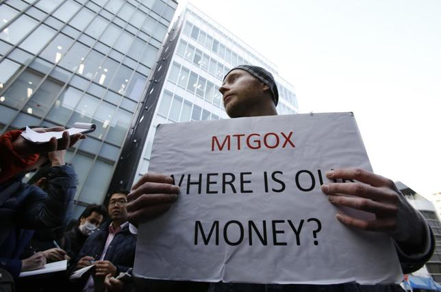 Kolin Burges, a self-styled cryptocurrency trader and former software engineer from London, holds a placard to protest against Mt. Gox, in front of the building where the digital marketplace operator was formerly housed in Tokyo February 26, 2014. REUTERS/Toru Hanai