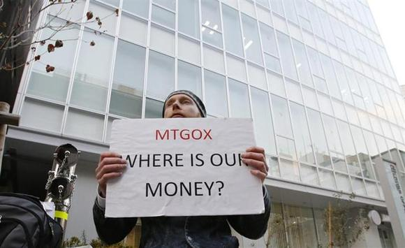 Kolin Burges, a self-styled cryptocurrency trader and former software engineer who came from London, holds a placard to protest against Mt. Gox, in front of the building where the digital marketplace operator is housed in Tokyo February 25, 2014. REUTERS/Toru Hanai
