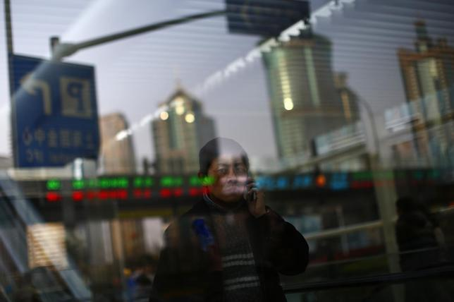 A man walks out of a subway station as he talk on the phone at the financial district of Pudong in Shanghai March 11, 2014. REUTERS/Carlos Barria