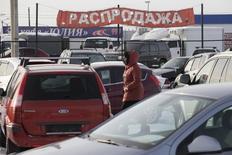 """Женщина на авторынке """"777"""" близ Красноярска 15 января 2013 года. Минпромторг РФ прогнозирует сокращение авторынка в 2014 году минимум на 2,8 процента до 2,83 миллиона штук из-за девальвации рубля, снижения цен на нефть и сокращения покупательской способности населения, сказал замминистра промышленности и торговли Алексей Рахманов. REUTERS/Ilya Naymushin"""
