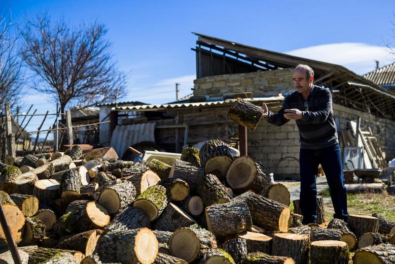 A Crimean Tartar piles up wood in his garden in Belogorsk near the Crimean capital of Simferopol March 17, 2014. REUTERS/Thomas Peter