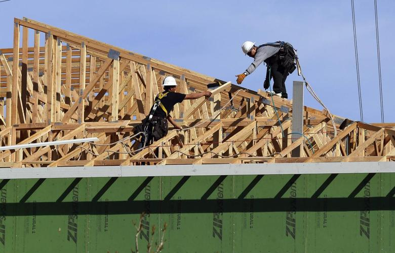 Workers install a roof on a multi-family building in Broomfield, Colorado February 19, 2014. REUTERS/Rick Wilking