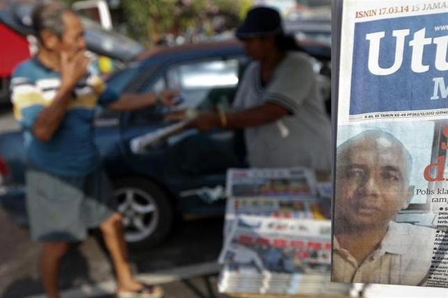 A front page picture of Zaharie Ahmad Shah, the pilot of the missing Malaysia Airlines MH370, is seen at a stand as a man buys newspapers in Dengkil, near Kuala Lumpur International Airport March 17, 2014. REUTERS/Damir Sagolj