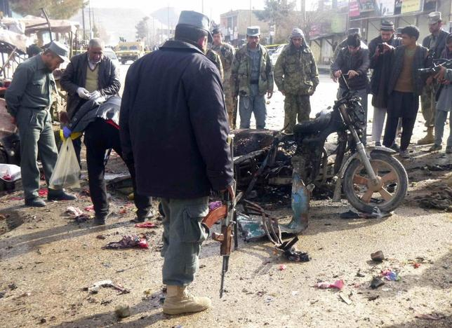 An Afghan police officer stands at the site of a suicide blast in Faryab, northern Afghanistan March 18, 2014. The suicide bomber killed 15 people and wounded at least 28 in the attack on a busy marketplace in Faryab on Tuesday, the provincial governor said. REUTERS/Stringer