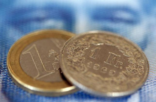 An one euro coin and an one Swiss franc coin are seen on a one hundred Swiss franc note, in this picture illustration taken in Zurich August 8, 2011. REUTERS/Christian Hartmann