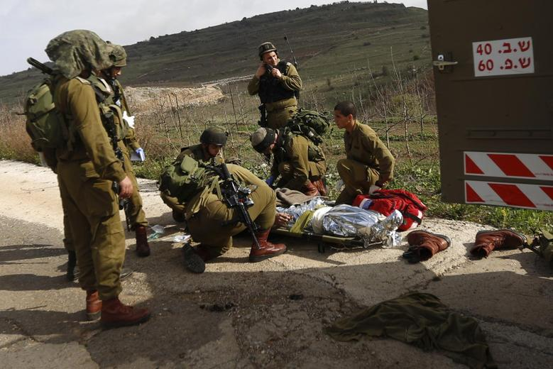 Israeli soldiers evacuate their comrade who was wounded during an explosion near the Druze village of Majdal Shams in the Golan Heights March 18, 2014. REUTERS/Jinipix
