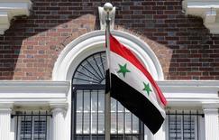 Флаг Сирии у посольства ближневосточной страны в Вашингтоне 29 мая 2012 года. Вашингтон предписал посольству и консульствам Сирии прекратить работу на территории США; сирийские дипломаты и сотрудники, не являющиеся американскими гражданами, должны покинуть страну. REUTERS/Kevin Lamarque