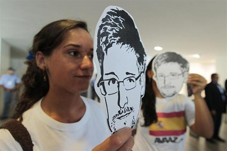 Activists from advocacy group Avaaz hold illustrations of former U.S. spy agency NSA contractor Edward Snowden as they deliver a petition to the Itamaraty Palace in Brasilia February 13, 2014. REUTERS/Joedson Alves/Files