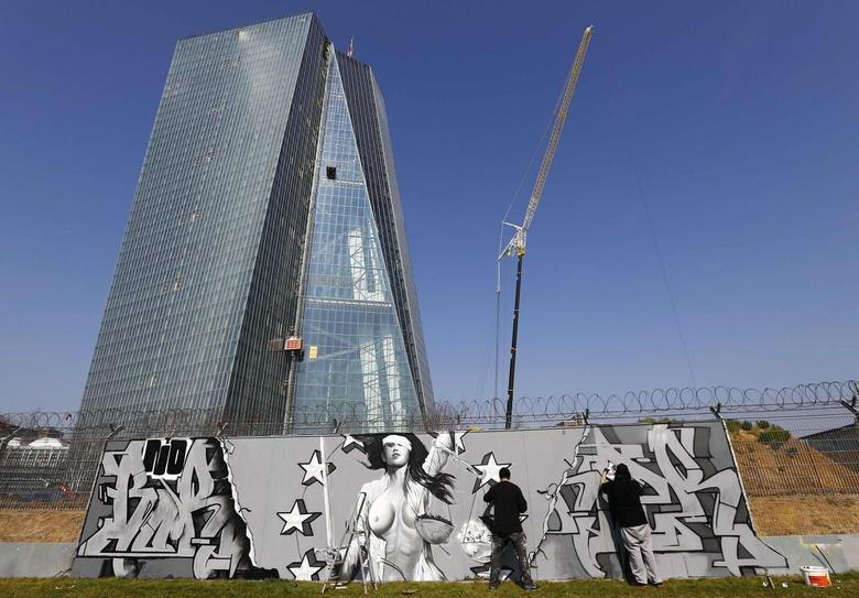 Artists Justus Becker, aka COR (L) and ''Bobby Borderline'' work on their graffiti mural on a fence surrounding the construction site for the new head quarters of the European Central Bank (ECB) in Frankfurt, March 14, 2014. REUTERS/Kai Pfaffenbach