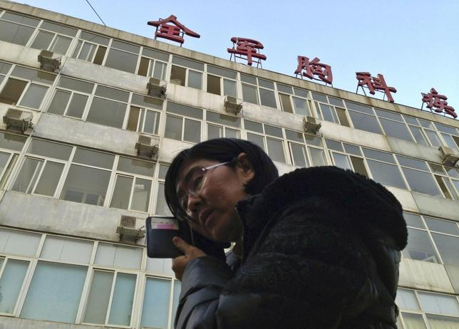 Wang Yu, the lawyer of human right activist Cao Shunli, talks on the phone in front of a hospital building where Cao is hospitalized at its intensive care unit in Beijing March 1, 2014. REUTERS/Kim Kyung-Hoon