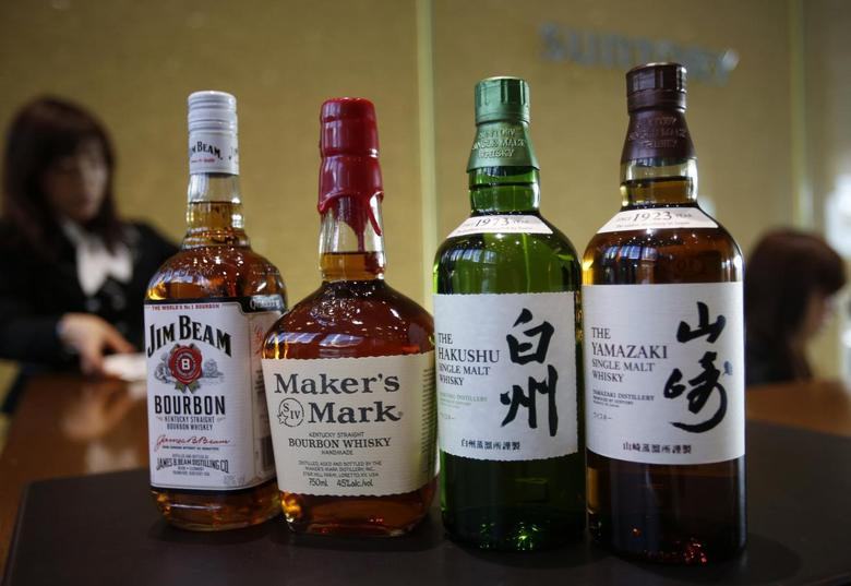 Bottles of Suntory Holding's Yamazaki (R) and Hakushu (2nd R) whiskies are displayed with Beam Inc's Jim Beam (L) and Maker's Mark bourbon at the entrance of Suntory World Headquarters in Tokyo January 14, 2014. REUTERS/Issei Kato