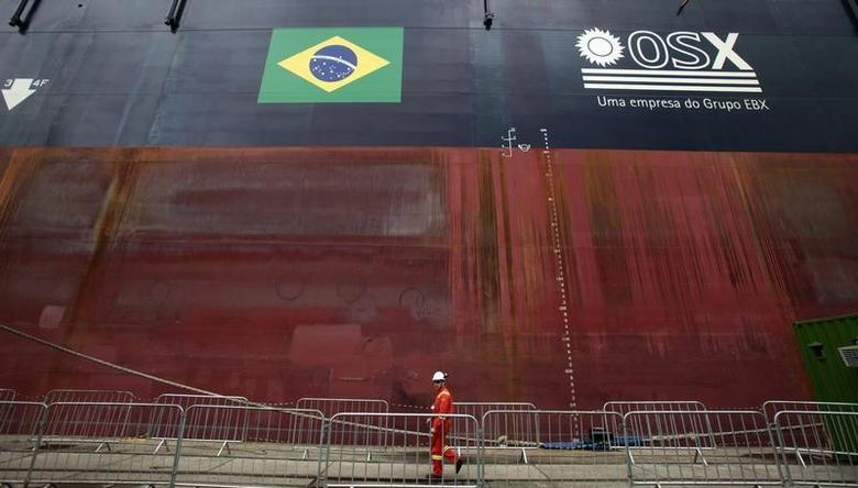 A worker walks past in front of FPSO OSX-1, the first floating production, storage and offloading unit in OSX's fleet, anchored at the port of Rio de Janeiro November 17, 2011. REUTERS/Sergio Moraes