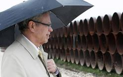 Joe Oliver, Canadian minister of natural resources, waits to speak in the rain at the pipe yard for the Houston Lateral Project, a component of the Keystone pipeline system in Houston, Texas March 5, 2014. REUTERS/Rick Wilking