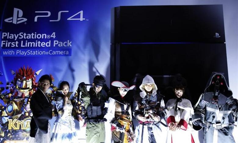 People wearing costumes of Playstation's game characters pose in front of an advertisement board for PlayStation 4 game consoles before its domestic launch event outside the Sony Showroom in Tokyo February 21, 2014. REUTERS/Yuya Shino/Files