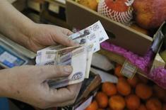 Продавщица пересчитывает купюры на рынке в Москве 3 марта 2014 года. Рубль стабилен утром среды, подорожав при открытии за счет возможных продаж экспортной выручки в преддверии крупных налоговых выплат. REUTERS/Maxim Shemetov