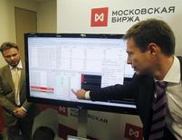 Сотрудники Московской биржи демонстрируют экран с показателями индексов в Москве 15 февраля 2013 года. После двух дней роста российских акций, которые участники рынка склонны списывать преимущественно на закрытие коротких позиций, падение возобновилось. REUTERS/Maxim Shemetov (RUSSIA - Tags: BUSINESS)