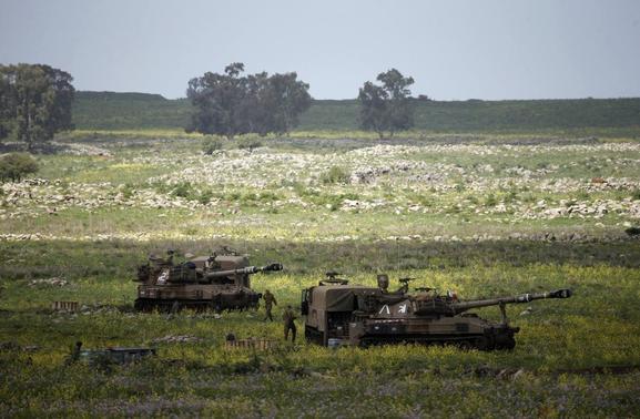 Israeli soldiers walks beside mobile artillery units near the city of Katzrin in the Golan Heights March 19, 2014. REUTERS-Ronen Zvulun