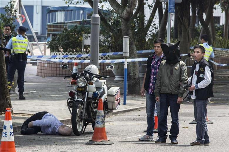 A suspect, seen walking next to a dummy of former Ming Pao chief editor Kevin Lau, is taken away by the police after the reconstruction of a crime scene at Sai Wan Ho in Hong Kong, March 18, 2014. REUTERS/Tyrone Siu