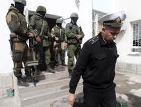 Украинский офицер (справа) покидает штаб ВМФ в Севастополе 19 марта 2014 года. Три российских флага развеваются у входа в штаб украинского военно-морского флота в Севастополе после того, как, по словам очевидцев, пророссийские силы взяли под свой контроль как минимум часть объекта, не встретив вооруженного сопротивления. REUTERS/Vasily Fedosenko