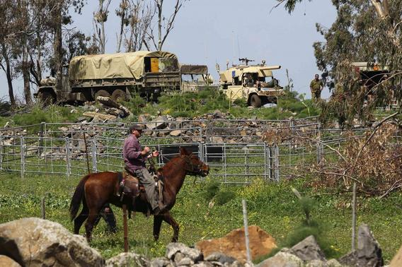 A man rides a horse past Israeli soldiers on the Golan Heights March 19, 2014. REUTERS-Ronen Zvulun