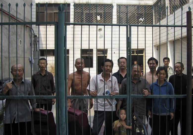 Detained petitioners stand behind prison gates at Nanyang city's office on the outskirts of Beijing September 10, 2007. REUTERS/Chris Buckley