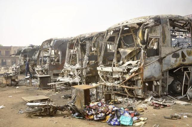 A man providing security walks past the charred remains of buses after Monday's explosions at a bus park in Sabon Gari in Kano March 19, 2013. REUTERS/Stringer