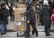 Um entregador da FedEx com um carrinho cheio de pacotes, na 5th Avenue em Nova York. A FedEx, a segunda maior companhia de entrega de pacotes do mundo, divulgou resultados piores que o esperado nesta quarta-feira e estimou que o lucro para o ano inteiro será mais baixo, dizendo que sofreu um impacto significativo com as tempestades de inverno. 26/12/2013 REUTERS/Carlo Allegri