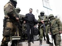Um oficial da Marinha ucraniana deixa a base naval em Sebastopol. Tropas russas apoiadas por voluntários desarmados ocuparam nesta quarta-feira a sede naval da Ucrânia na localidade portuária de Sebastopol, na Crimeia, onde hastearam a bandeira russa. 19/03/2014 REUTERS/Vasily Fedosenko