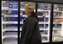 Un cliente pasa junto a un refrigerador casi vacío en Lilburn, EEUU, feb 12 2014. El déficit de la cuenta corriente de Estados Unidos se desplomó al mínimo en 14 años en el cuarto trimestre del año pasado ya que las exportaciones alcanzaron un récord, mostró el miércoles un reporte gubernamental. REUTERS/Tami Chappell