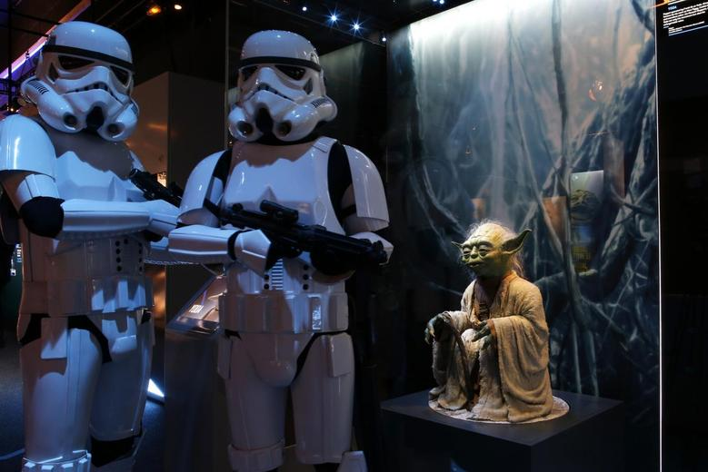 Performers dressed as Imperial Stormtroopers characters pose in front of a model of character Yoda from the Star Wars film series during press day for the exhibit ''Star Wars Identities'' at the ''Cite du Cinema'' movie studios in Saint-Denis, near Paris, February 13, 2014. REUTERS/Benoit Tessier