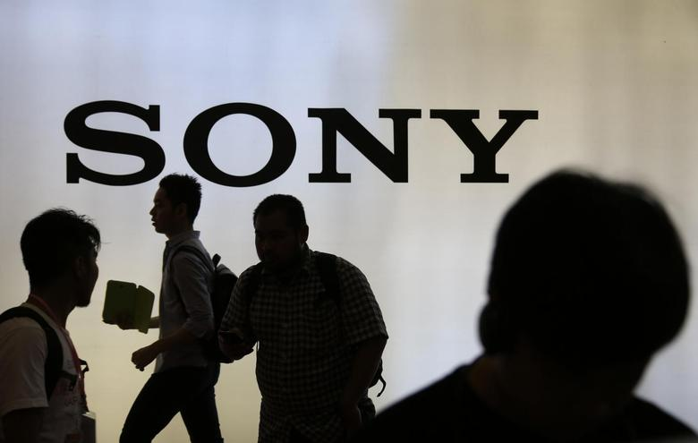 Indonesian youth walk near a Sony sign during Digital Imaging expo in Jakarta, March 5, 2014. REUTERS/Beawiharta