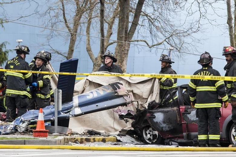 Firefighters investigate the crash of a KOMO News helicopter, which killed KOMO news photographer Bill Strothman and pilot Gary Fitzner near the Space Needle in Seattle, Washington March 18, 2014. REUTERS/David Ryder