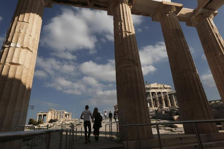 Visitors walk through Propylaia, the ancient Acropolis gateway, as the Parthenon temple (R) is seen in the background in Athens November 19, 2013. REUTERS/John Kolesidis
