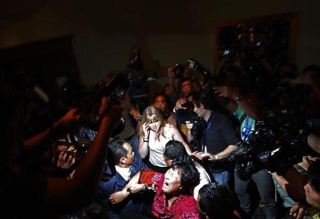 A Chinese family member of a passenger onboard the missing Malaysia Airlines Flight MH370 screams as she is being brought into a room outside the media conference area at a hotel in Kuala Lumpur International Airport March 19, 2014. REUTERS/Edgar Su