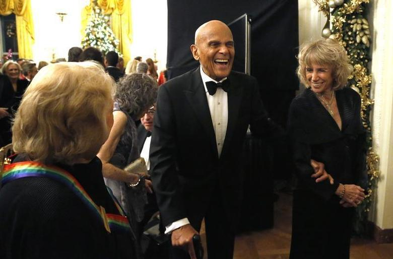 Harry Belafonte (C) laughs with a fellow audience member as they depart after a reception for the 2013 Kennedy Center Honors recipients at the White House in Washington, December 8, 2013 file photo. REUTERS/Jonathan Ernst