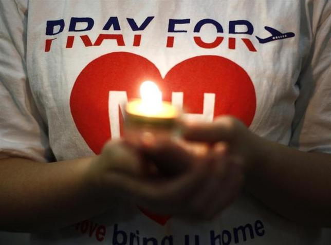 A woman holds a candle during a special prayer for passengers onboard the missing Malaysia Airlines Flight MH370 at the Chinese Assembly Hall in Kuala Lumpur March 19, 2014. REUTERS/Samsul Said