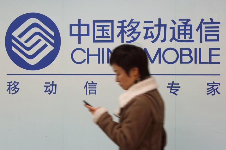 A woman looks at the screen of her mobile phone while walking past a China Mobile sign in downtown Shanghai December 18, 2013 file photo. REUTERS/Aly Song