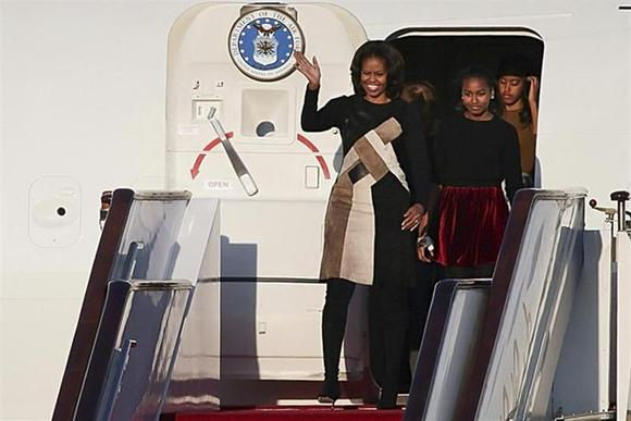 U.S. first lady Michelle Obama (L) waves as she walks out the plane with her daughters Sasha (2nd R) and Malia (R) upon their arrival at Beijing Capital International Airport in Beijing, March 20, 2014. REUTERS/China Daily