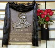 The hall of fame brass plaque honoring country music singer Johnny Cash is draped in black with red roses at the side at the County Music Hall of Fame and Museum in Nashville, Tennessee, September 12, 2003.