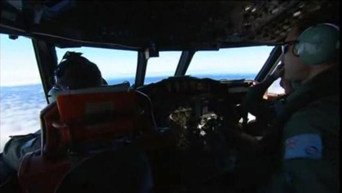 Personnel working on board Royal Australian Air Force (RAAF) P3 Orion aircraft are pictured during a sea search for the missing Malaysia Airlines flight MH370 in an area between Australia, southern Africa and Antarctica, in this still image taken from video March 20, 2014. REUTERS/ via REUTERS TV/Pool