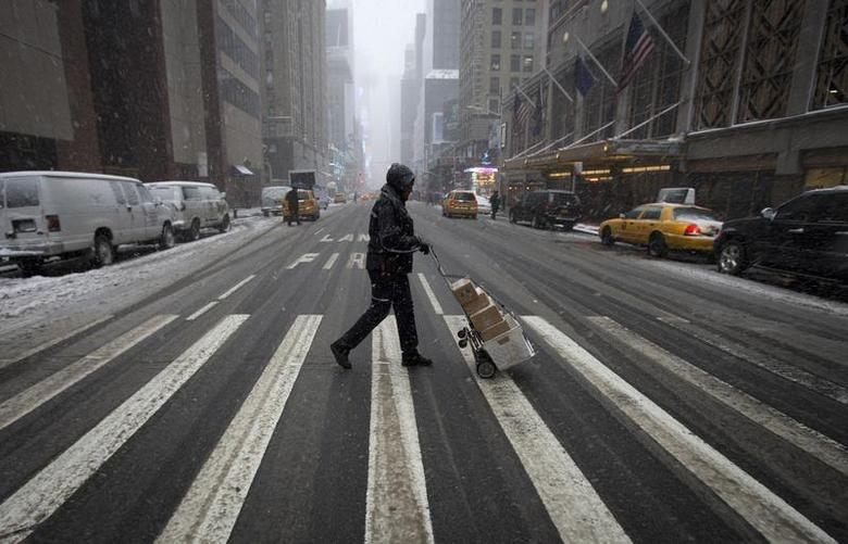 A delivery person walks through Times Square as it snows in the Manhattan borough of New York February 3, 2014. REUTERS/Carlo Allegri