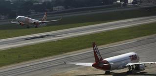 Um Boeing 737-800 da Gol decola enquanto um Airbus A320 da TAM aterrisa no aeroporto de Congonhas, em São Paulo. A demanda por voos domésticos no Brasil registrou aumento de 11,2 por cento em fevereiro sobre igual mês de 2013, segundo dados das quatro maiores empresas aéreas do país compilados pela associação que representa o setor, a Abear, nesta quinta-feira. 17/01/2014 REUTERS/Nacho Doce