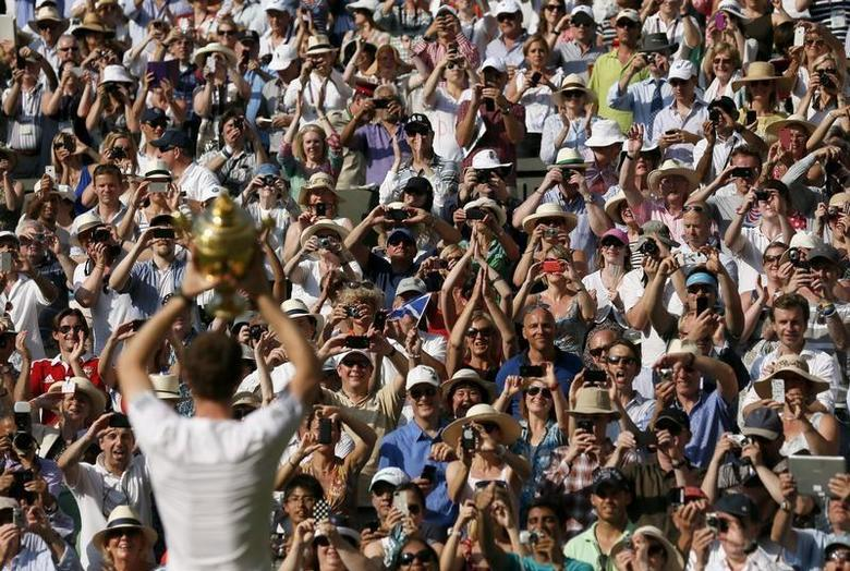 Andy Murray of Britain holds the winners trophy up to the spectators after defeating Novak Djokovic of Serbia in their men's singles final tennis match at the Wimbledon Tennis Championships, in London July 7, 2013. REUTERS/Stefan Wermuth