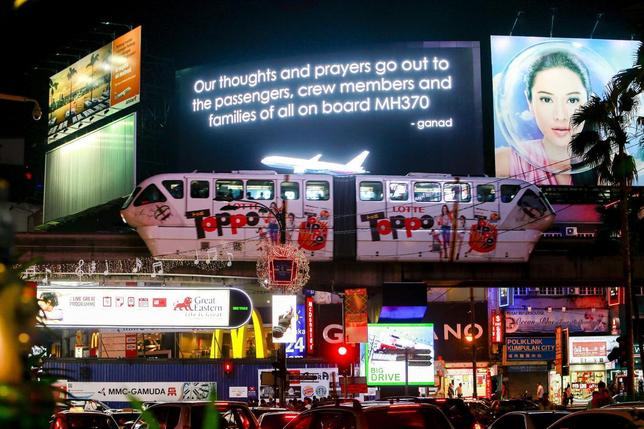 A message for passengers onboard the missing Malaysia Airlines Flight MH370 is seen on big screen in Kuala Lumpur March 20, 2014. REUTERS/Samsul Said