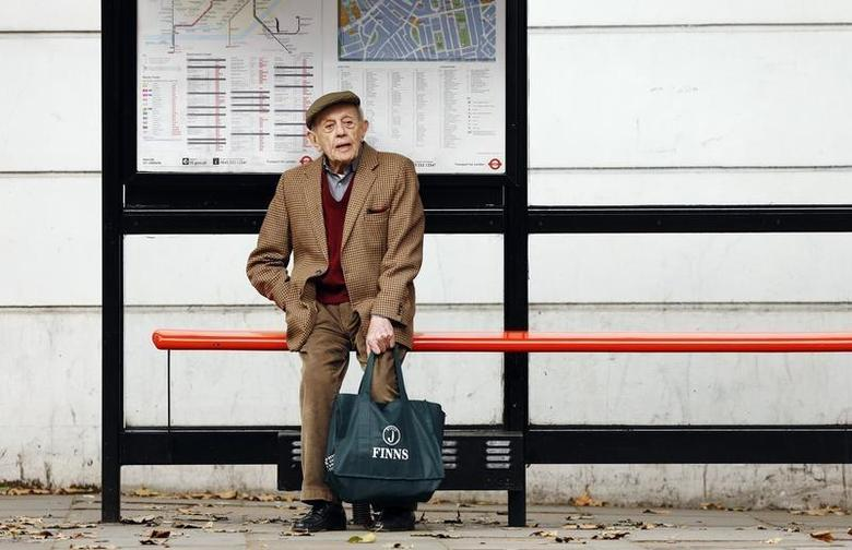 A man sits by himself at a bus stop in London October 18, 2013. REUTERS/Luke MacGregor
