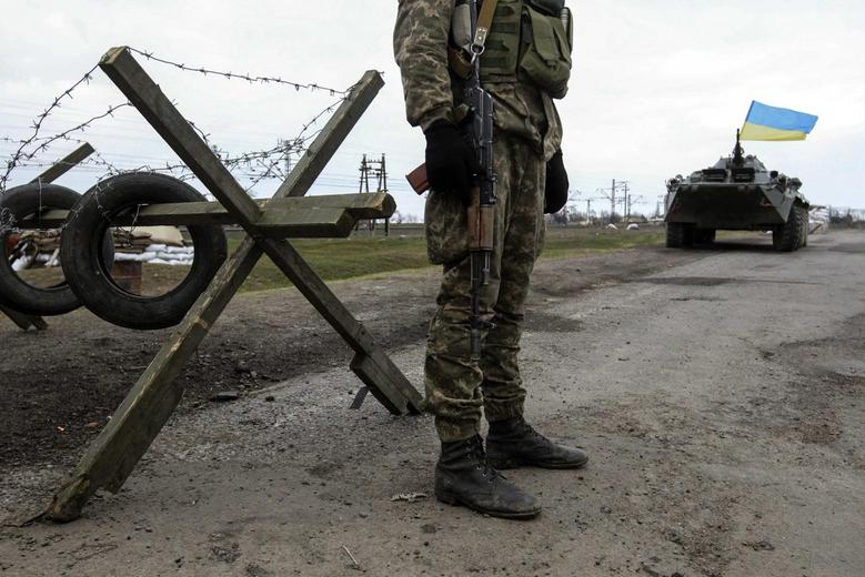 A Ukrainian soldier and armored personnel carrier guard a checkpoint near the village of Salkovo, in the Kherson region adjacent to Crimea, March 20, 2014. REUTERS/Valentyn Ogirenko