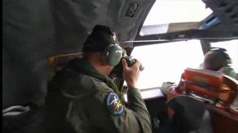 A crewman looks out of the window on board Royal Australian Air Force (RAAF) P3 Orion aircraft during a sea search for the missing Malaysia Airlines flight MH370 in an area between Australia, southern Africa and Antarctica, in this still image taken from video March 20, 2014. REUTERS/ via REUTERS TV/Pool