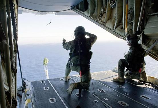 Royal Australian Air Force (RAAF) Loadmasters, Sergeant Adam Roberts (L) and Flight Sergeant John Mancey, launch a 'Self Locating Data Marker Buoy' from a C-130J Hercules aircraft in the southern Indian Ocean during the search for missing Malaysian Airlines flight MH370 in this picture released by the Australian Defence Force March 21, 2014. REUTERS/Australian Defence Force/Handout