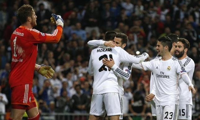 Real Madrid's Alvaro Morata (2nd L) is congratulated by teammates after scoring a goal against Schalke 04 during their Champions League last 16 second leg soccer match at Santiago Bernabeu stadium in Madrid March 18, 2014. REUTERS/Paul Hanna